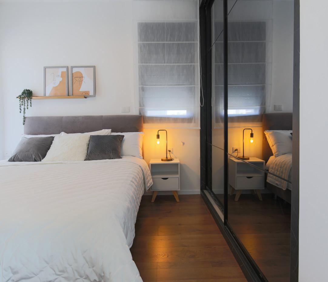 חדר שינה הורים עם ארון מראה.