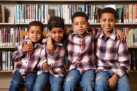 Four brothers read and play together at Hillsdale Library.