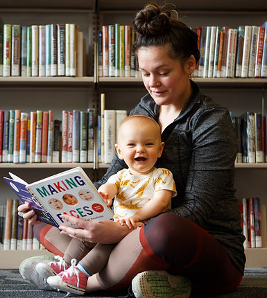 Early literacy begins wih a trusted adult, a book, and a child. This mother and baby are reading together at Multnomah County Library