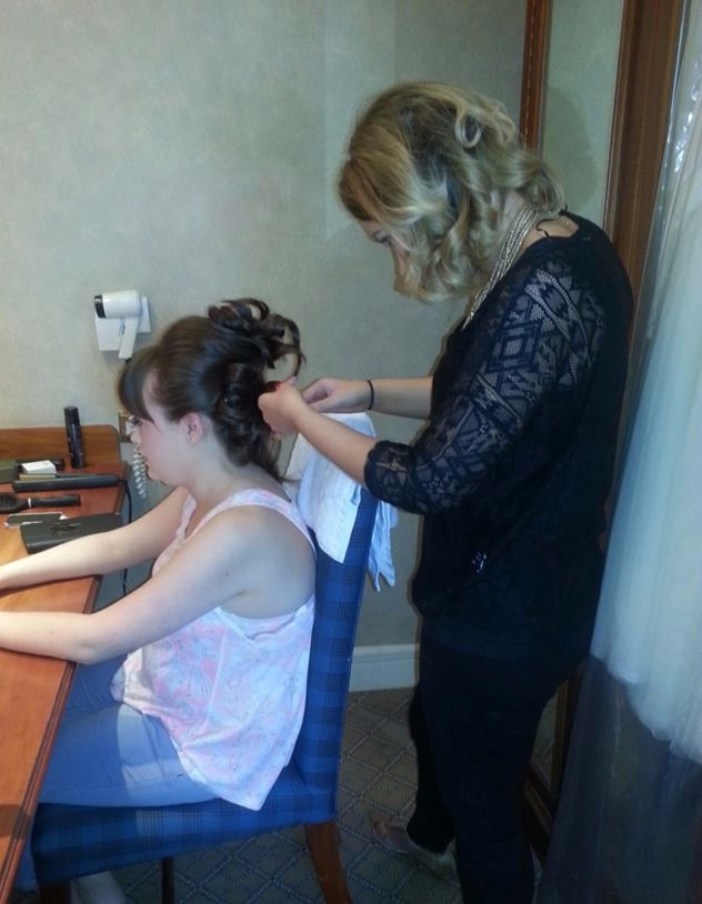 wedding hairdresser completing neat bridal hair up style to brunette bride