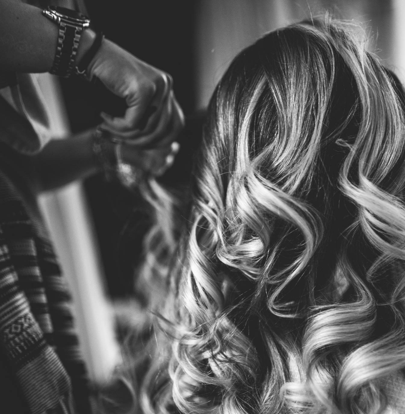 wedding hairdresser finishing touches on curly wedding hairstyle