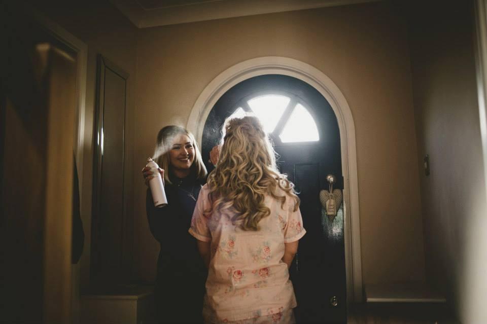 wedding hair stylist spraying curly half undo wedding hair into place