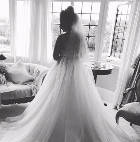 Glamorous bride wearing cathedral length veil, wedding dress and wedding hair in a high bun.