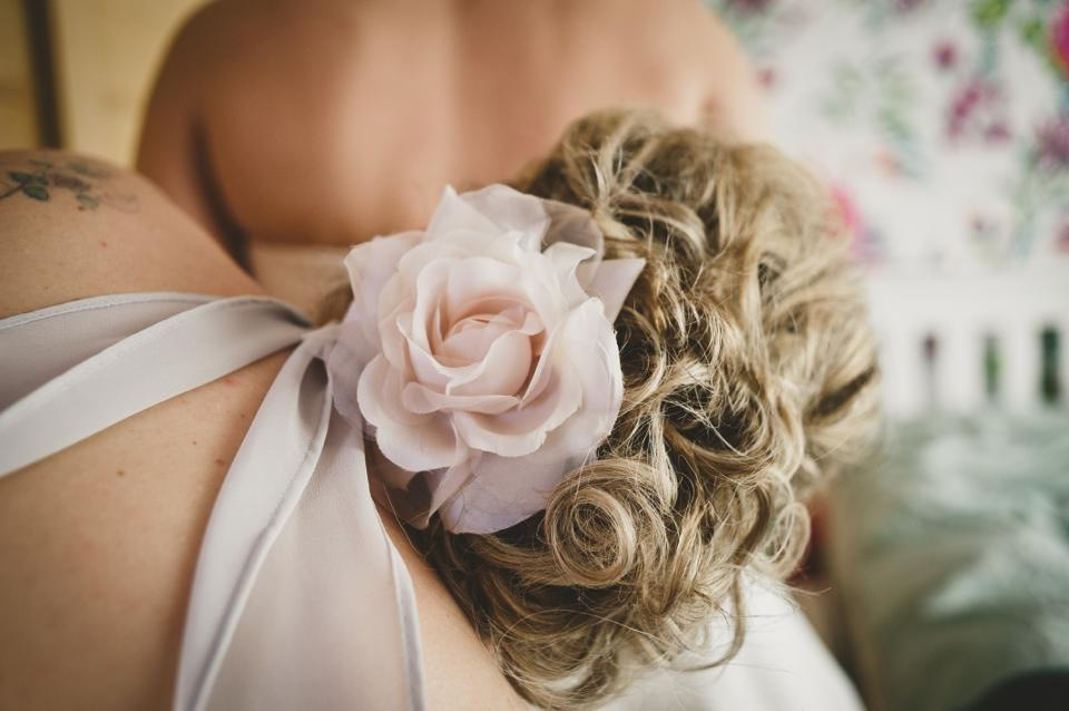 bridesmaid fixing brides dress, natural curly bridesmaid hair with flower hair accessory