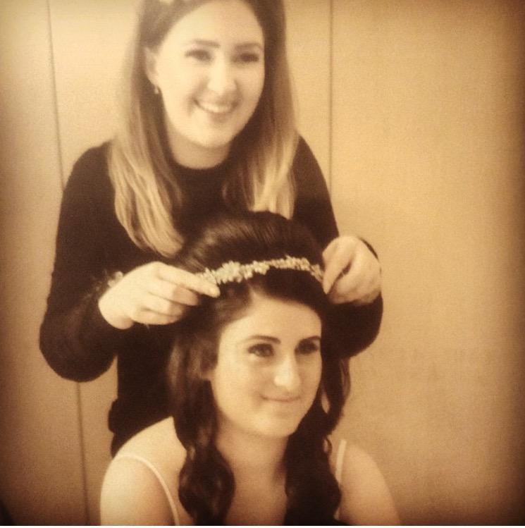 wedding hairdresser adding sparkling tiara to wedding hair half updo for brides hairstyle