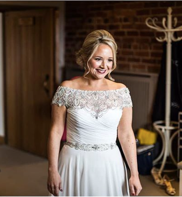 beautiful bride wearing Justin Alexander gown with elegant bridal hair up at Curradine Barns