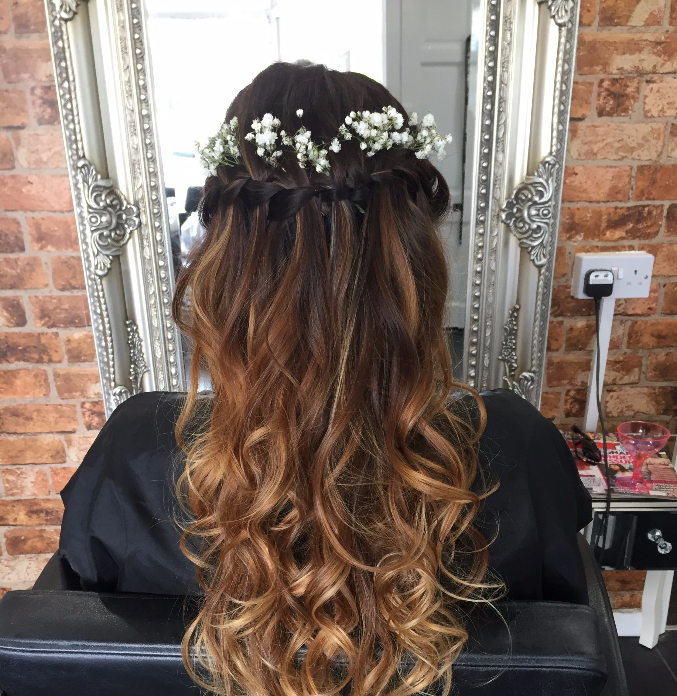 wedding hair with natural curls left in loose wave with half undo finished with flowers in the hair