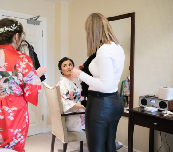 bridal hairdresser finishing touches for stunning bride and bridesmaids completing wedding hair for