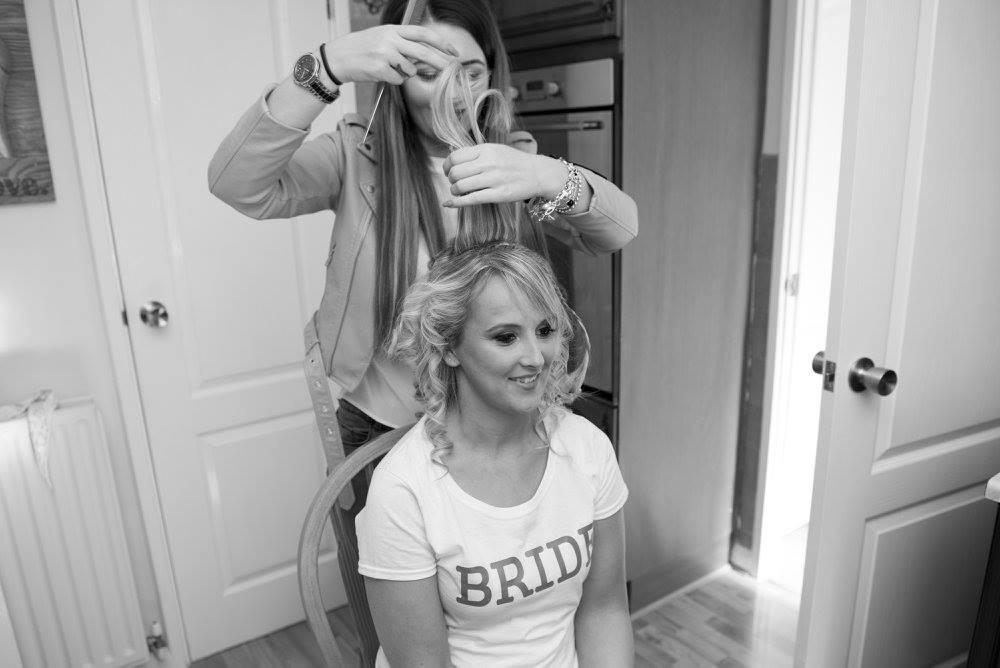 wedding hair specialist doing brides hair on wedding morning, long bridal blonde hair