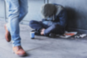 Homeless man sitting on the street in th