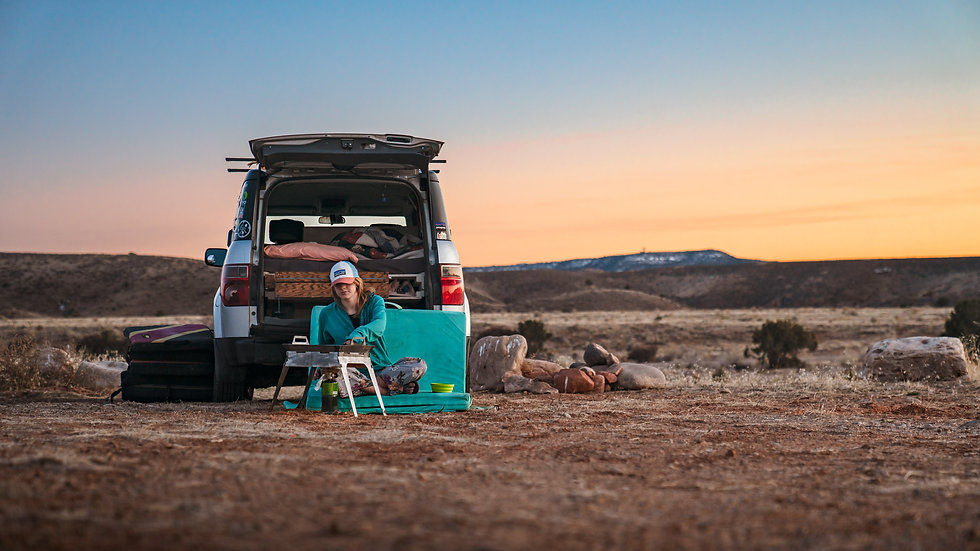 Emily cooking while car camping in Moab, Utah cooking with the Travel Your Own Road Overland Skriddle cookware set