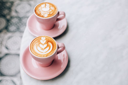 Two beautiful pink cups of cappuccino wi
