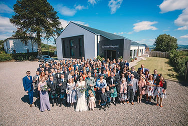wedding pary outside Gartmore Village Hall on a sunny day