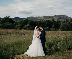 bride and groo looking into each others eyes, hills in background