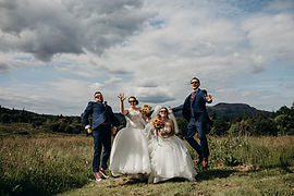two happy couples jumping in he air at a double wedding