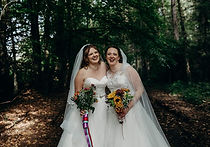two brides with bouquets at double wedding