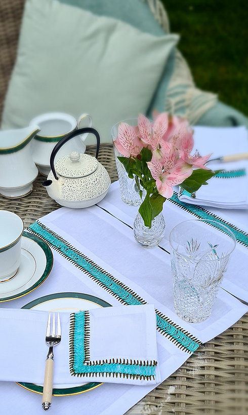Table setting with handmade green embroidered placemats and cloth napkins