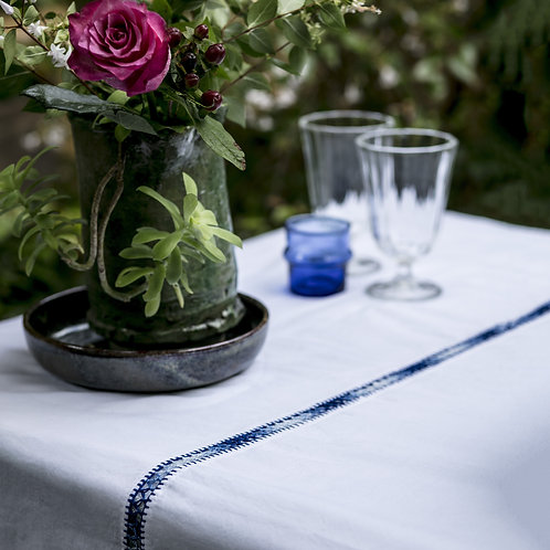 table setting with blue embroidered table runner