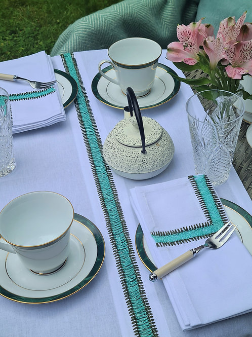 table setting of green embroidered napkin and table runner