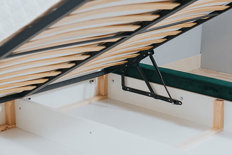 A closeup shot of a bed with wooden frame and lifting mechanism for a storage space.jpg