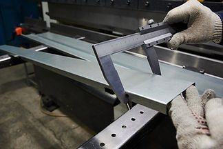 A specialist at the factory measures the accuracy of bending of  metal sheet used as a cov