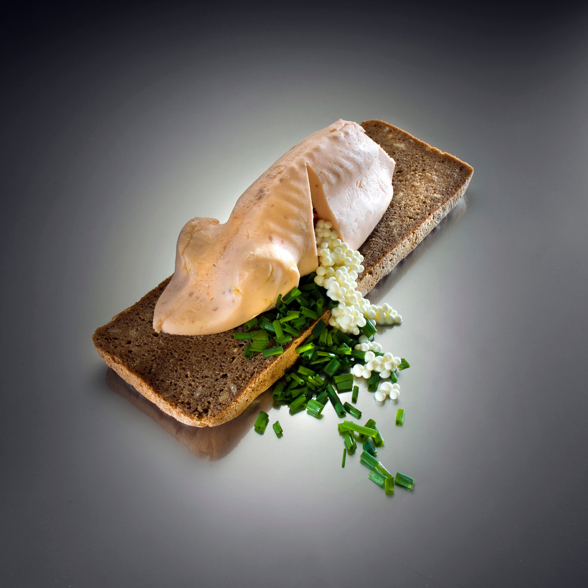 Gefilte fish -Main dishes; Salmon mousse filling with sour pearl, cream pearls and carrots pearl.  Salmon, pickled cucumber, carrots and Irit cream served on a bread