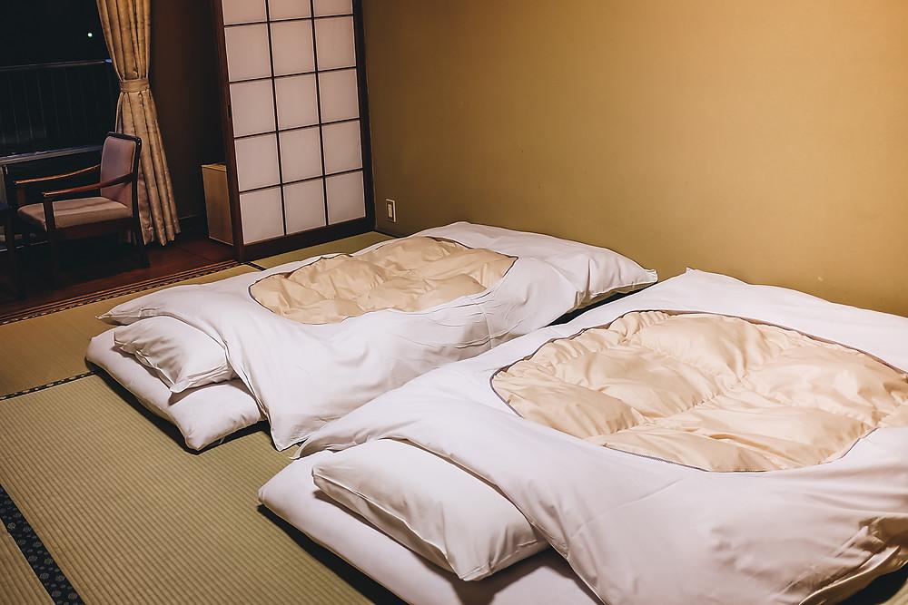 Interior do Ryokan com colchão futon branco na esteira de tatame