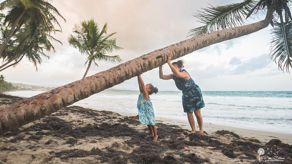 mère et fille redressant un cocotier