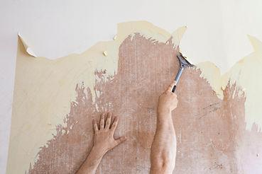 Person scraping wallpaper