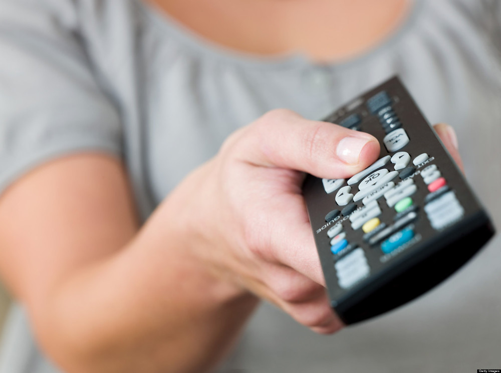 A woman pointing a remote control