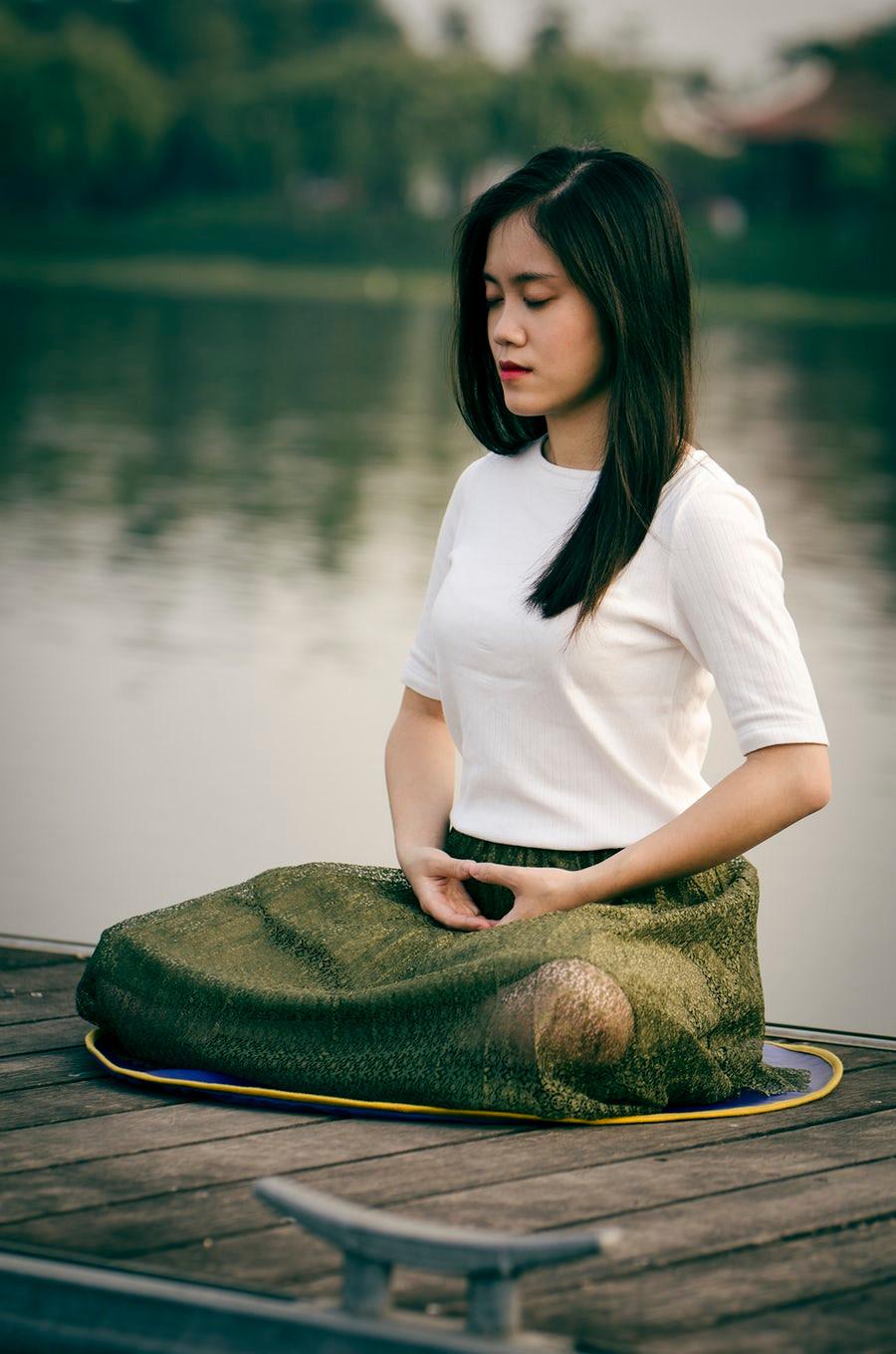 Na imagem, mulher praticando meditação com o Mandala Mudra.