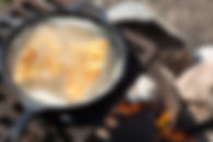 Canva - Fish frying in cast iron pan on