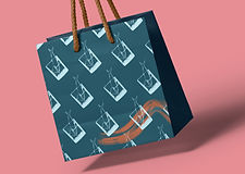 """Unique packaging design for the Taste of Kintyre tourism company showing a dark teal shopping bag printed with a repeating pale blue pattern of the brand's signature """"fish in a glass"""" illustration and a burnt orange wave swoosh at the bottom right hand corner. The bag has natural rope handles and is shown against a dusty pink background."""