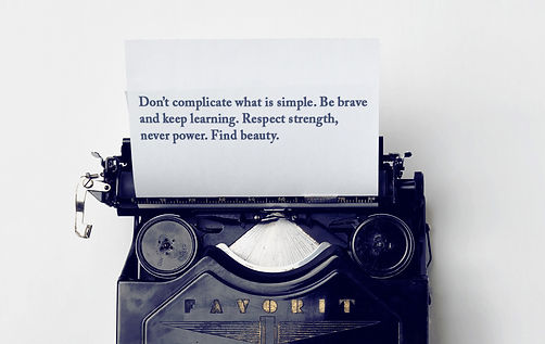 """In Bold company values typed on a navy blue old fashioned typewriter. The white sheet sticking out of the typewriter reads """"Don't complicate what is simple. Be brave and keep learning. Respect strength, never power. Find beauty."""""""