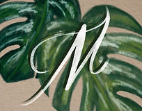 White hand drawn letter M on an illustrated background of green leaves.