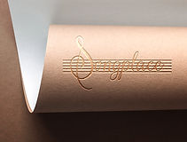 """Music cafe logo design printed on natural brown card. The logo is the word """"Songplace"""" with the S shaped like a Musial note and the letters arranged over five horizontal bars like written music. The logo is embossed into the card with a pale gold foil finish."""