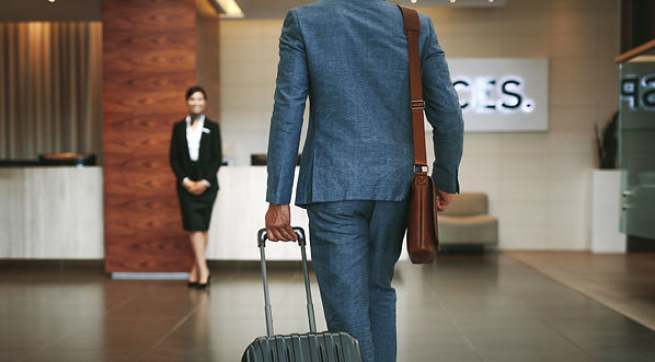 Business man walking into hotel with luggage.