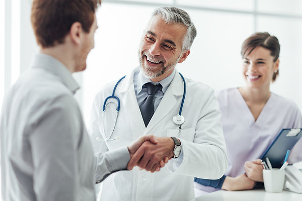 Doctor shaking hands with a patient nurse in background