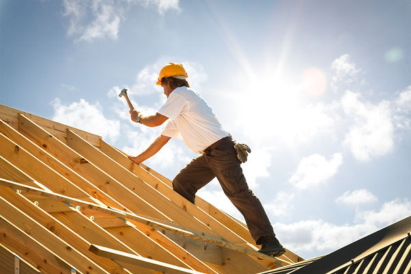 Construction worker building roof on sunny day