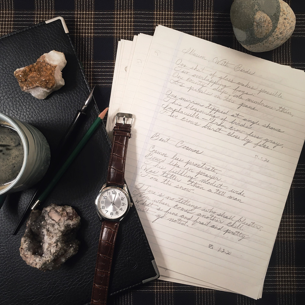 Photograph: flat lay of writing supplies, coffee, a wrist watch, and desk rocks. Ruled sheets of poetry written in light, penciled cursive.