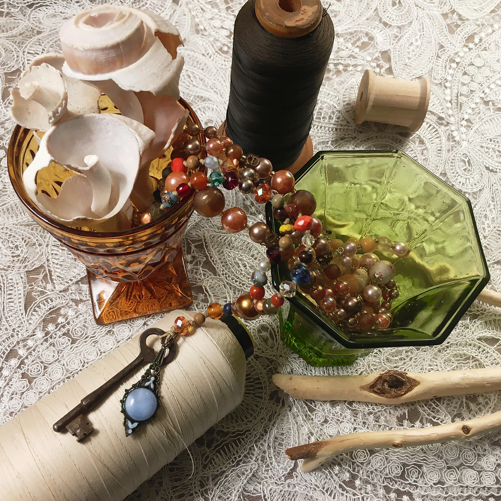 Photograph: vintage flat lay on a white lace background. Two glass desert goblets in the center. The amber glass holds three broken whelk shells, cracks as to reveal their inner spirals. Plastic pearl jewelry spills from the gold goblet to the green one. One necklace ends in a rusty skeleton key and filigree charm pendant, set with a sky blue stone. To the sides, antique spools of thread and beaver-chewed sticks from a woods.
