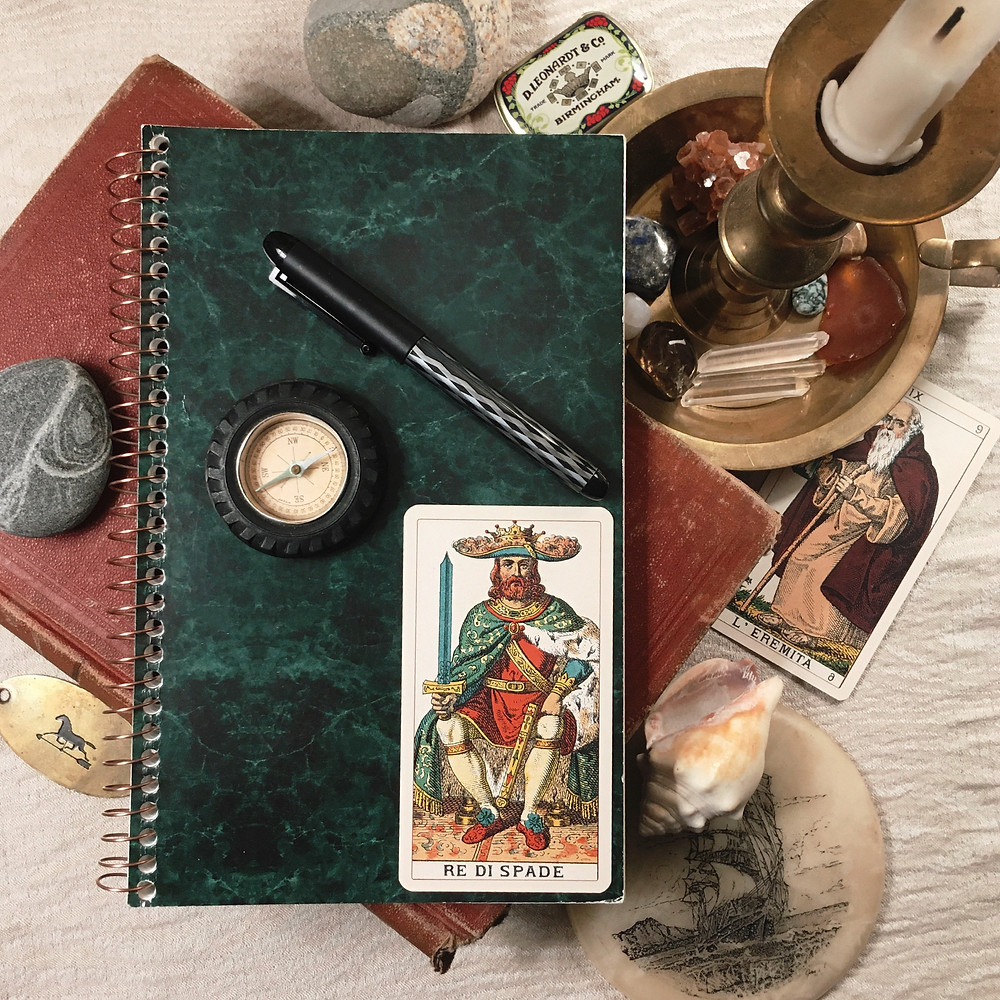 Photograph: flat lay of notebook and pen, old books, candle, vintage kitsch (a ship, a shell, a compass, a horse, an arrow), and tarot cards (The King of Swords and The Hermit).