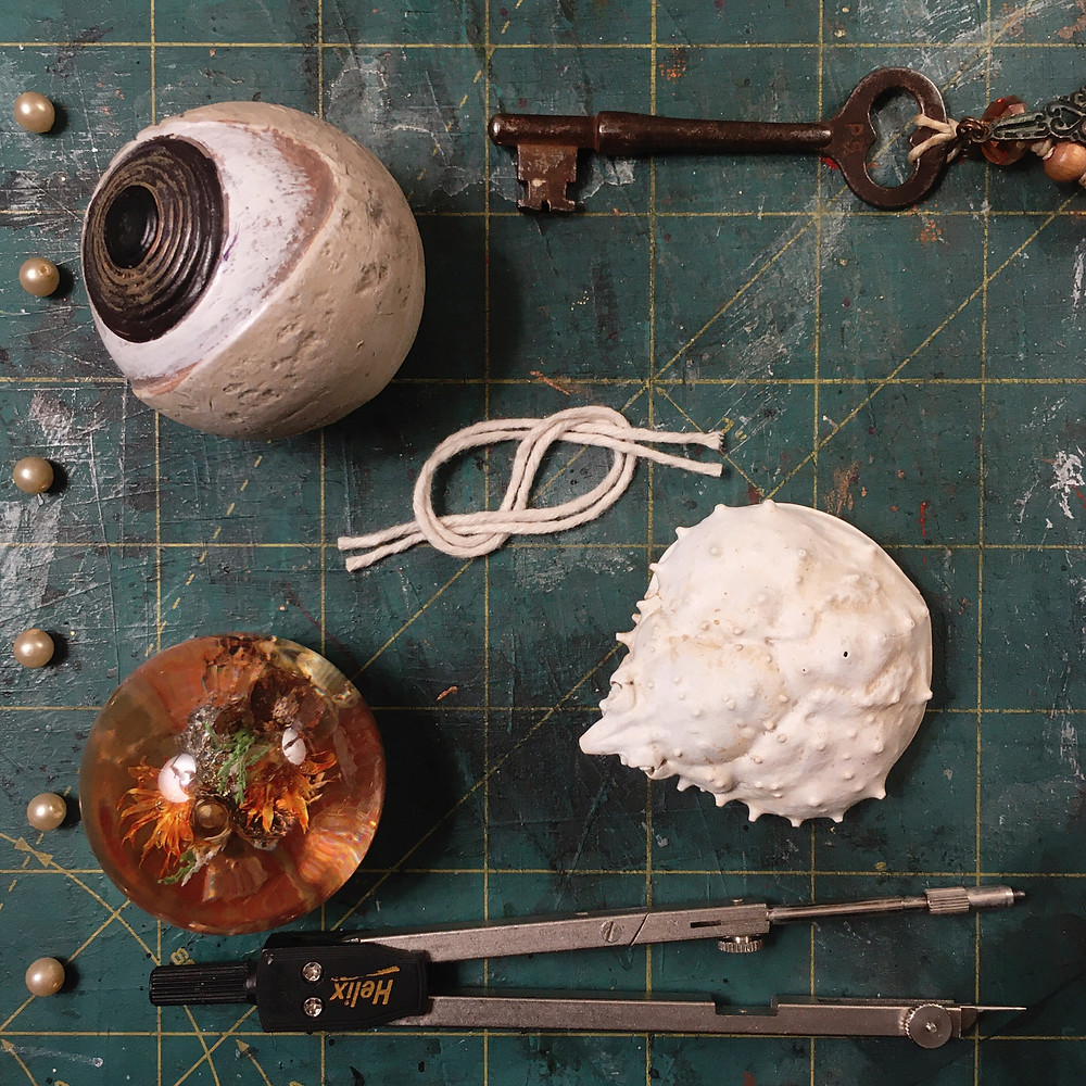 Photograph: flat lay of symbolic objects arranged on a gridded, green cutting mat, as though in a list, with plastic pearl beads as the bullet points. A key, an eyeball figurine, a loose knot of twine, a sun-bleached crab shell, a tiny, vintage resin globe with flowers and greenery suspended in the center, and a drafting compass.