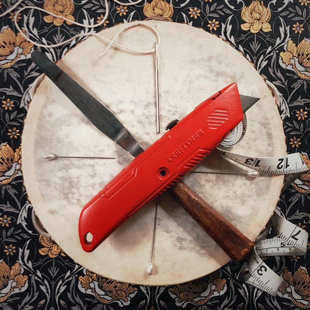 Photograph: Flay lay of red utility knife, palette knife, tapestry needle and twine, curling measuring tape, and vintage pins laid in compass rose pattern on top of a tambourine over a gold and black, floral fabric background.