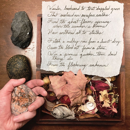 Photograph: a handwritten scrap from An Unquiet Grave, over an open wooden trinket box full of dried leaves, roses, and paper wasp's nests. To the left, a specimen of pyrite in slate, a black and orange marble beach stone, and a hand holding a rust-red rock with a fresh water stain.