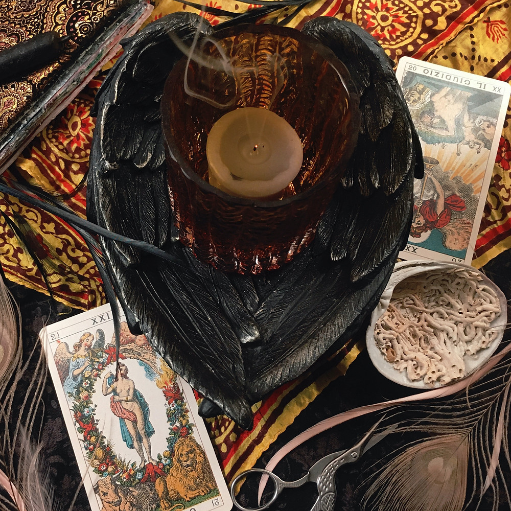 Photograph: Smoke rises from the smoldering wick of a snuffed-out candle in a bowl shaped of carved, black wings, surrounded by symbolic trinkets. A black candle, black poultry feathers and pink peacock feathers, crane embroidery scissors, a clamshell full of marine worm tubes, a red and gold silk scarf, and the tarot cards Judgement and The World.