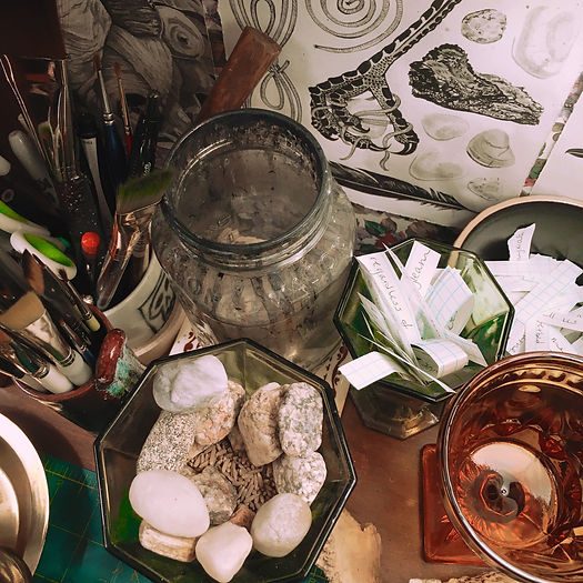 Photograph: a messy art desk covered in paintbrush and pen cups, and glassware full of incense ashes and paper scraps of cut-up words.