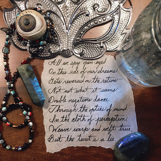 Photograph: Handwritten excerpt from Iris, framed by a silver paper fox mask with a grotesque eyeball figurine set in one socket, a strand of eye and window beads, blue light refracting through a watery paint jar, and labradorite stones.