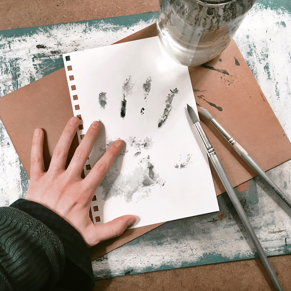 Photograph: art desk with the artist's hand leaving a gray watercolor handprint on a white sketchbook page.
