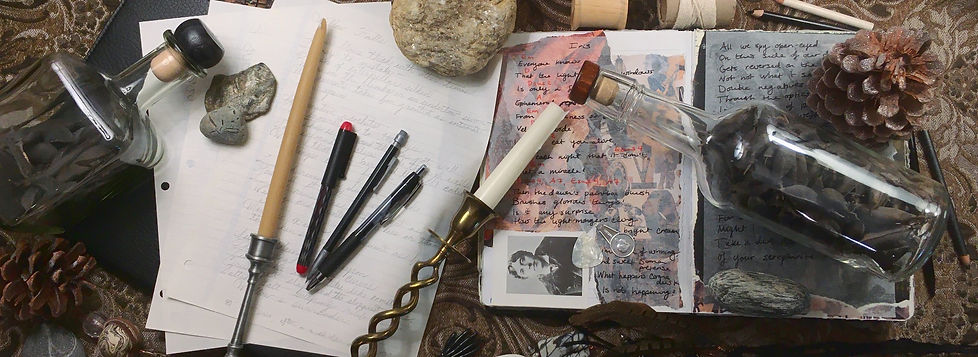 Photograph: a flat lay of writing supplies, handwritten poetry drafts, the songwriting book, desk rocks, candles, pinecones, and glass jars full of rattleweed pods.